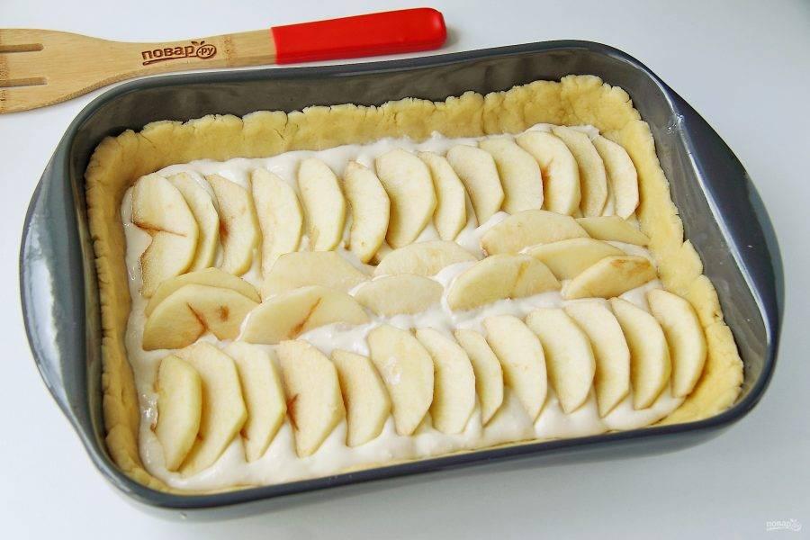 Сверху по творогу распределите нарезанные дольками яблоки. Отправьте форму в разогретую до 180 градусов духовку на 30 минут.