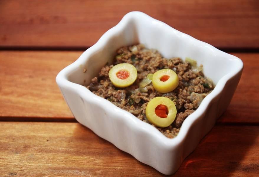 Возьмите посуду для запекания, выложите в неё фарш, сверху выложите оливки.  Емкость должна быть заполнена на три четверти.