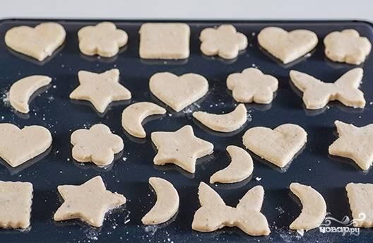 Вырежьте из теста печенья формочками и уложите их на противень, присыпанный мукой.