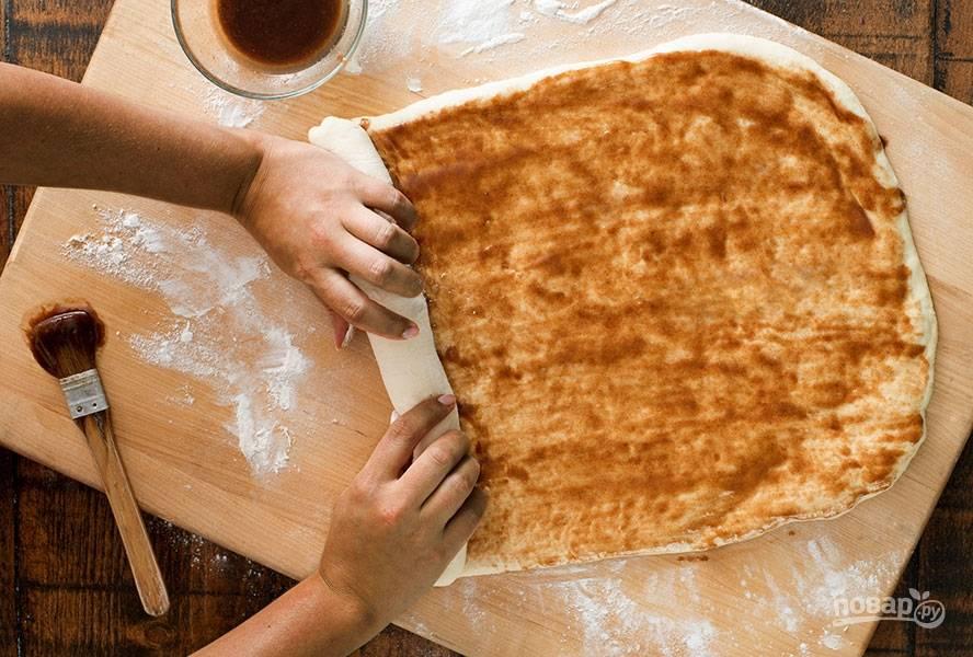 В отдельной емкости смешиваем коричневый сахар, корицу и сливочное масло до однородности. Распределяем эту смесь по поверхности теста. Аккуратно начинаем сворачивать тесто в рулет.
