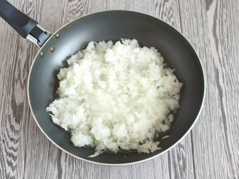 В сковороде разогрейте половину стакана растительного масла. Выложите лук, обжарьте до мягкости, помешивая.