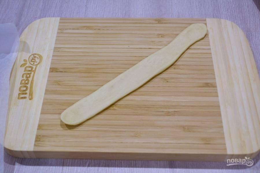 Из другого кусочка теста, размером с яйцо, раскатайте колбаску. Расплющите ее скалкой. С одной стороны нарежьте, чтоб получилась лапша по всей длине полоски, но не дорезайте до конца, чтоб ленточка у вас не развалилась.