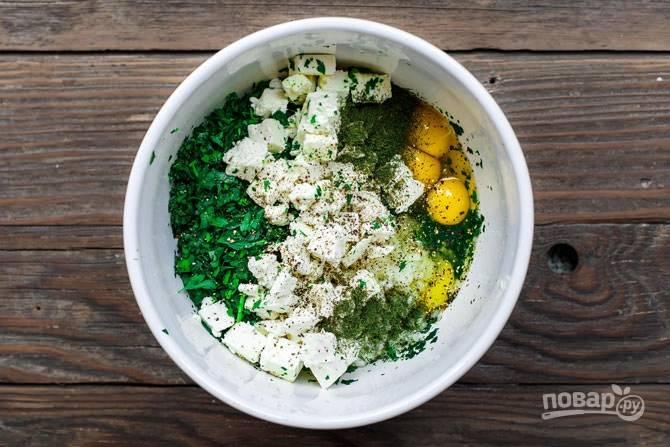 1. Включите духовку и разогрейте до 160 градусов. В глубокой мисочке соедините шпинат, измельченную зелень, лук, чеснок, сыр и яйца.
