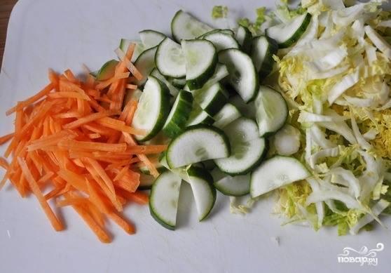 Все овощи вымойте и очистите, если необходимо. Морковку натрите на крупной терке или же нарежьте соломкой. Пекинскую капусту нашинкуйте как можно мельче. Затем добавьте огурец полукольцами. С него также можно предварительно снять кожицу.