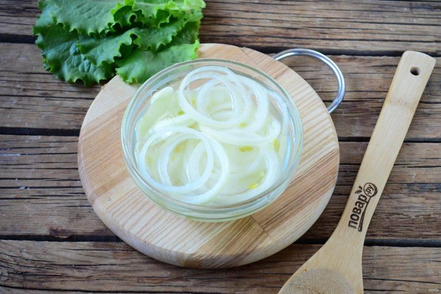 Пока шашлык в духовке, замаринуйте лук. Для этого каждую луковицу порежьте кольцами, сложите в небольшую пиалу. Смешайте воду с уксусом и залейте полученной жидкостью лук. Оставьте на 15-20 минут.