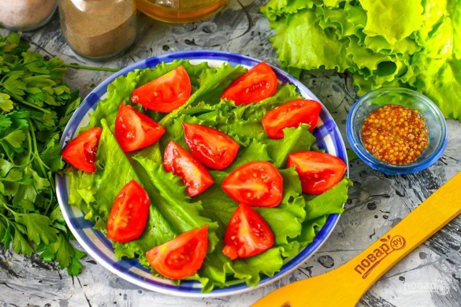 Помидоры черри промойте в воде, вырежьте из них сердцевинки и нарежьте пополам или на четвертинки. Выложите на листья салата.