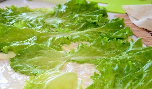 Теперь мы выкладываем листья салата на лаваш так, чтобы они немного выступали с одной стороны, а с другой наоборот было бы 10 см свободного места без начинки.