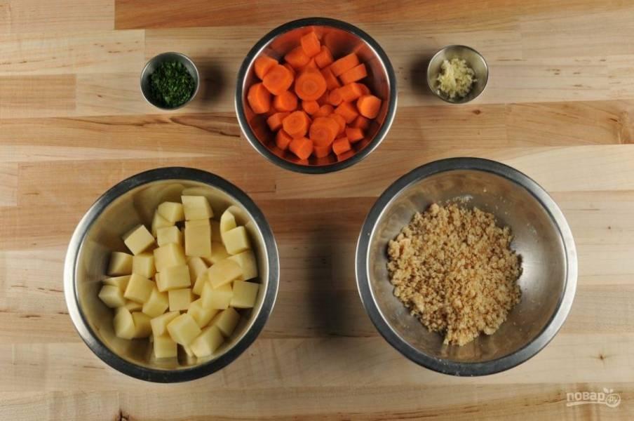 1. Подготовьте ингредиенты. Морковь почистите и нарежьте на толстые кружки. Измельчите петрушку и чеснок. Картофель нарубите крупными кубиками. Сухари обжарьте 40 секунд на сухой сковороде, а потом перетрите их с сыром, солью, перцем и большей частью петрушки.