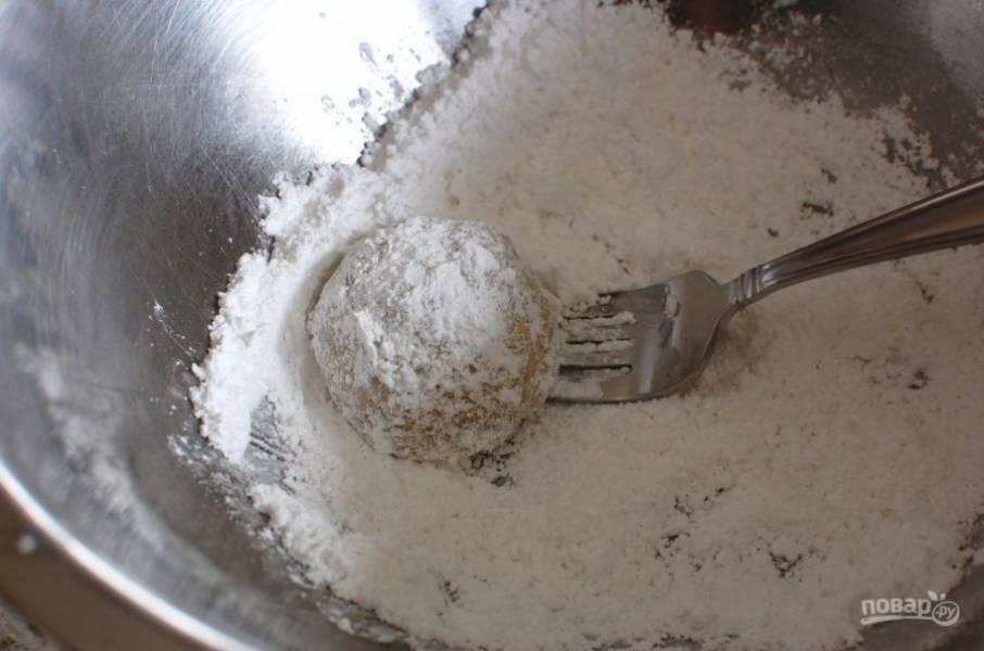 8.Готовое печенье достаньте из духовки и оставьте на 10 минут, затем в миску насыпьте сахарную пудру и каждое обваляйте в пудре.