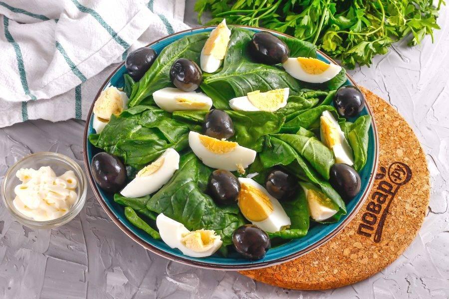 Выложите между яичной нарезкой маслины.