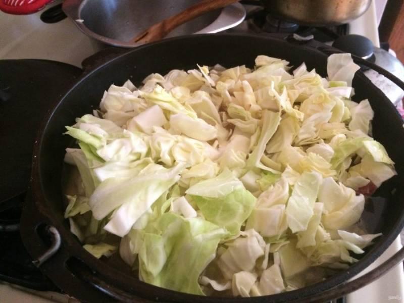 4.Нарежьте капусту кубиками, выложите ее в казанок, а также добавьте картофель, лавровый лист.