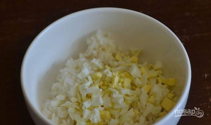В другую кастрюльку налейте холодную воду, положите в нее сырые куриные яйца и отварите их в крутую. Остудите яйца под струей холодной воды и очистите от скорлупы. Затем нарежьте их кубиками.
