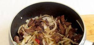Добавьте к мясу лук, жарьте еще 10 минут.
