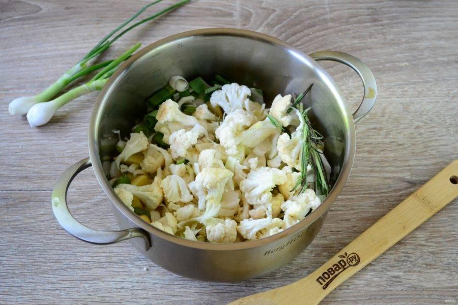 Сложите лук-порей и картофель в кастрюлю. Туда же положите цветную капусту, разделенную на мелкие соцветия. Добавьте соль, специи по вкусу, любую зелень, например петрушку, зеленый лук, розмарин и т. д.