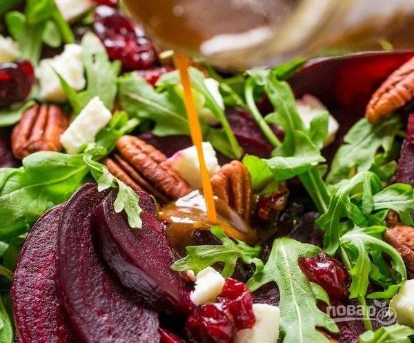 6. Смешайте рукколу, нарезанную свеклу, сыр, пекан и клюкву. Залейте салат соусом и подавайте к столу.