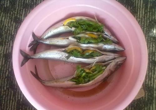 1. Рыбу разморозим, если нужно, вынимаем внутренности. Лимон и лук нарезаем колечками, и помещаем внутрь рыбы. Натираем каждую рыбу солью и перцем.