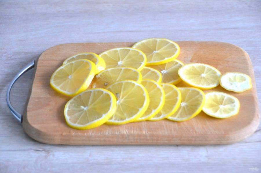 Пока варится сироп, хорошо промойте лимоны, нарежьте очень тонкими ломтиками, стараясь сохранить целостность ломтика.