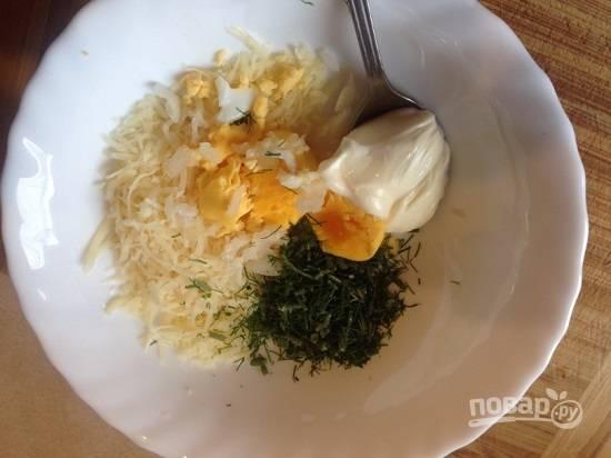 Желток смешиваем с мелко натертым сыром, измельченным укропом и майонезом. Добавим также измельченный чеснок.