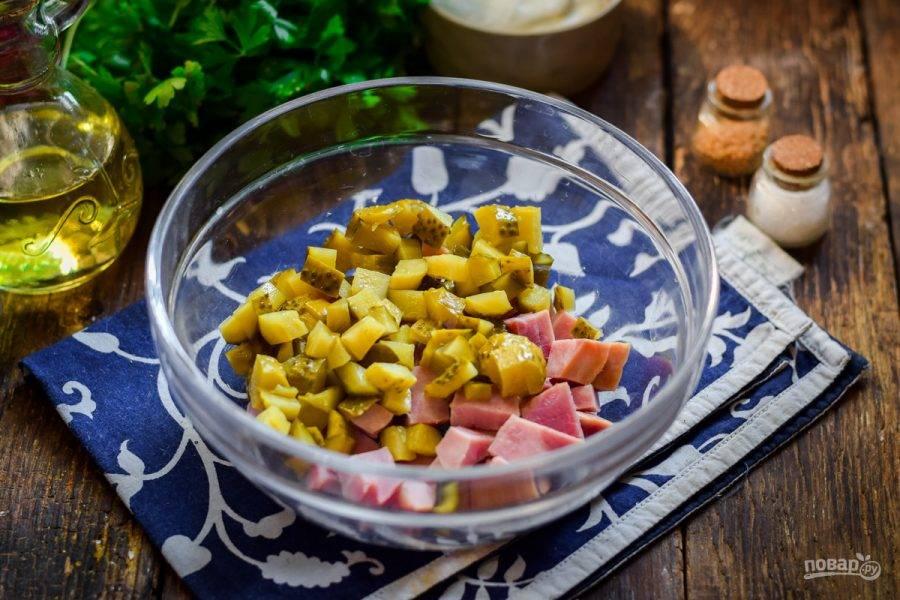 Нарежьте маринованные огурцы, добавьте в миску с ветчиной.