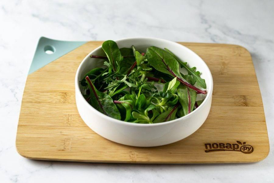 Салатные листья промойте, обсушите, выложите в тарелку.