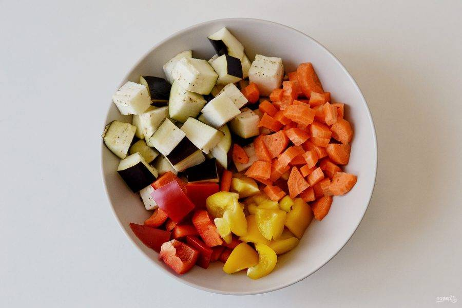 Для начала подготовьте овощи. Морковь очистите от кожуры, затем нарежьте все овощи (кроме помидоров) крупными кубиками.