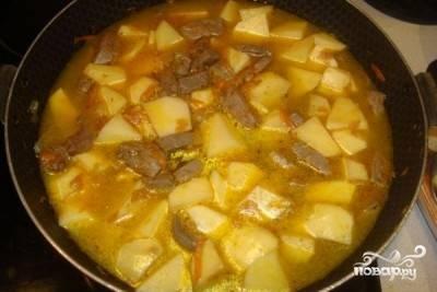 Нарезанный средними кусочками картофель добавьте к печени. Залейте все водой так, чтобы картошка была слегка покрыта водой. Добавьте еще немного соли и тушите под закрытой крышкой на медленном огне до готовности.