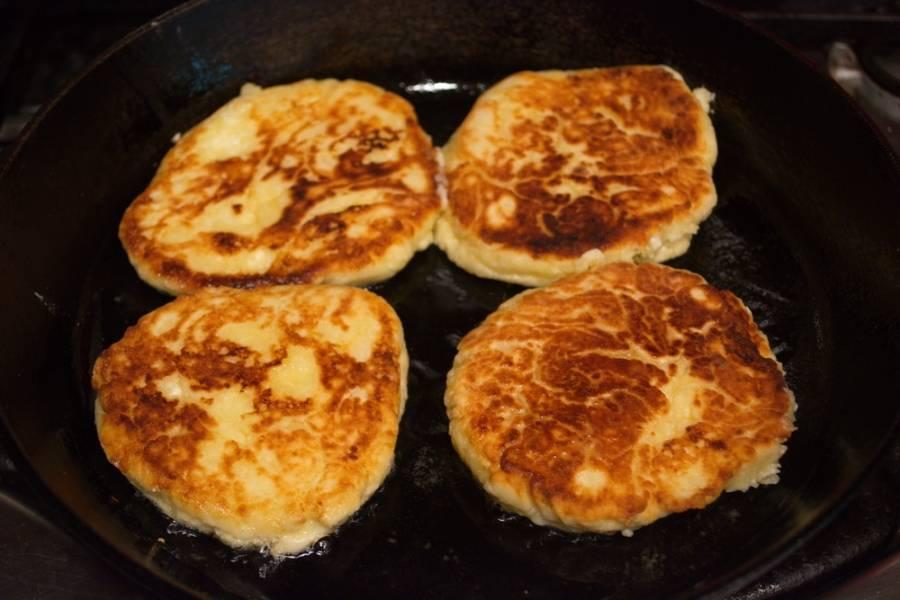 Сформируйте сырники. Каждый выложите на сковороду, добавив немного растительного масла. Обжарьте с двух сторон. Накройте крышкой сковороду, когда перевернете сырник на другую сторону.