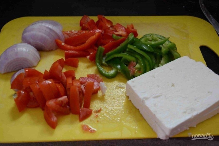 1.Вымойте томаты и нарежьте их небольшими кусочками. Очистите лук от кожуры и нарежьте его полукольцами. Очистите перцы от семян и нарежьте их полукольцами.