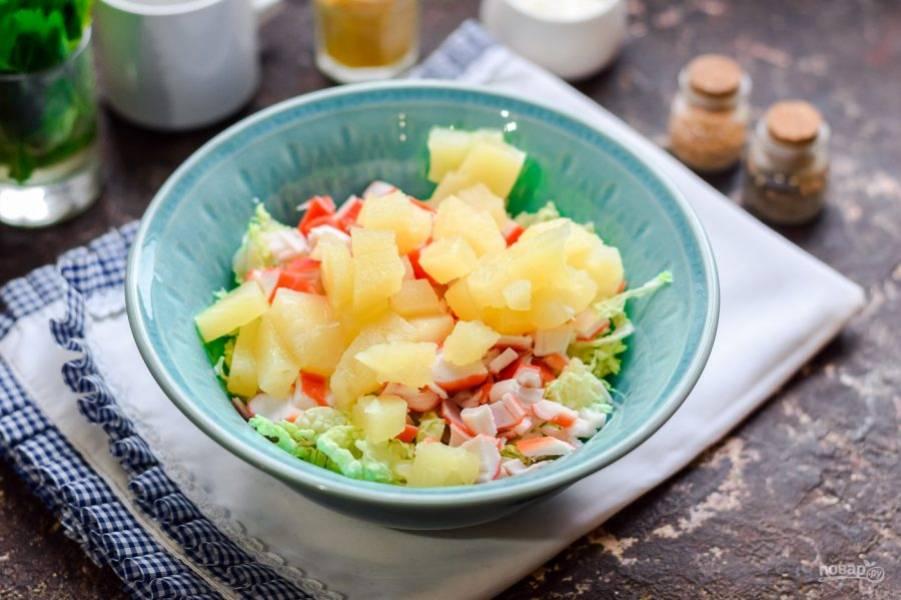 Следом нарежьте ананасы небольшими кубиками и переложите в салат.