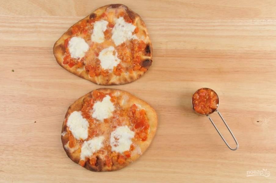 4. Затем лепёшки смажьте томатным соусом. Разложите порциями сыр. Запекайте лепёшки с начинкой ещё 5 минут.
