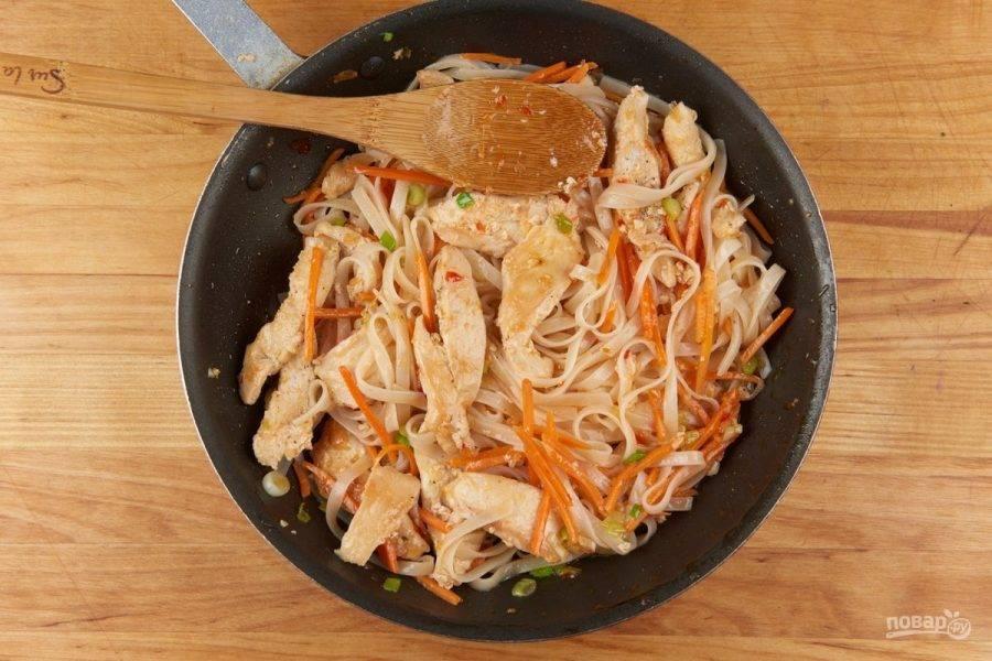 5. Далее переложите лапшу в сковороду к овощам. Добавьте курицу. Влейте соуса и немного масла. Готовьте блюдо 2 минуты, помешивая.