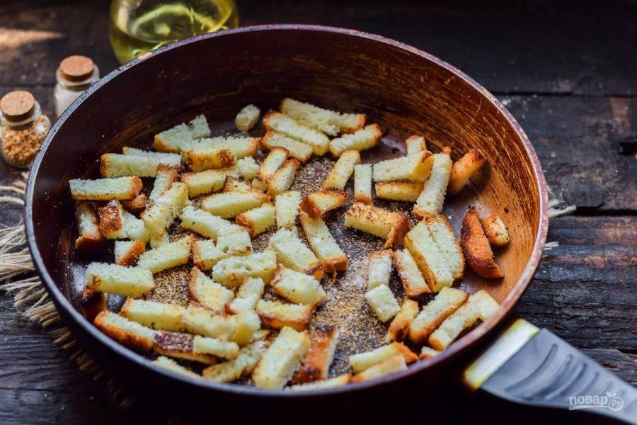 Жарьте гренки постоянно помешивая - 4-5 минут. В самом конце посыпьте все сухим чесноком, солью и перцем.