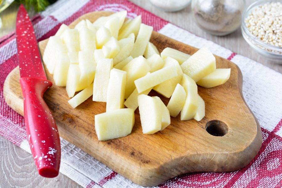 Почистите картофель и нарежьте его брусочками.