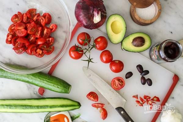 2. Нарежьте помидорки, измельчите луковицу. Авокадо вымойте, аккуратно извлеките косточку, а мякоть нарежьте кубиками.