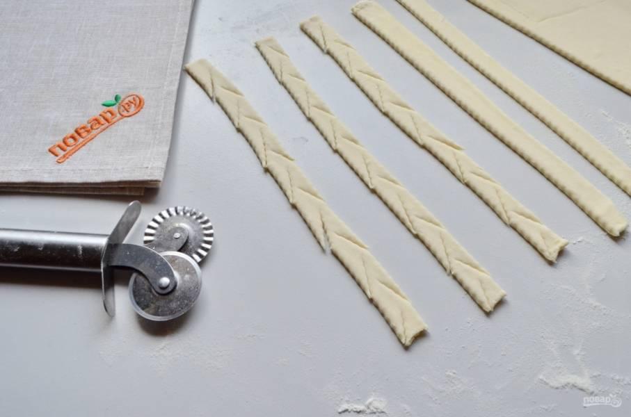 Слоенное тесто порежьте полосочками, каждую из которых оформите ёлочкой или как у меня — зигзагом.