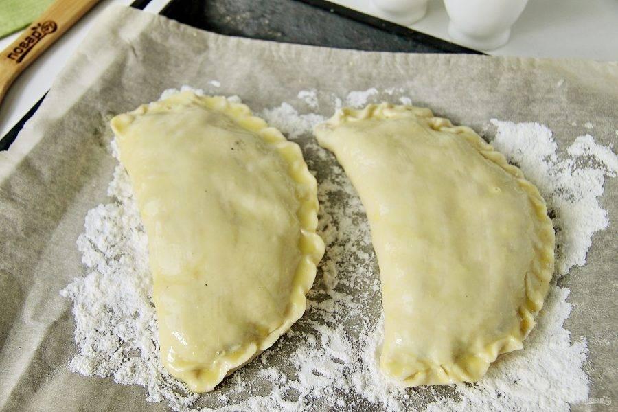 Противень застелите бумагой для выпечки, присыпьте ее мукой и выложите пироги. Смажьте поверхность взбитым желтком и отправьте в разогретую до 180 градусов духовку на 50-60 минут.