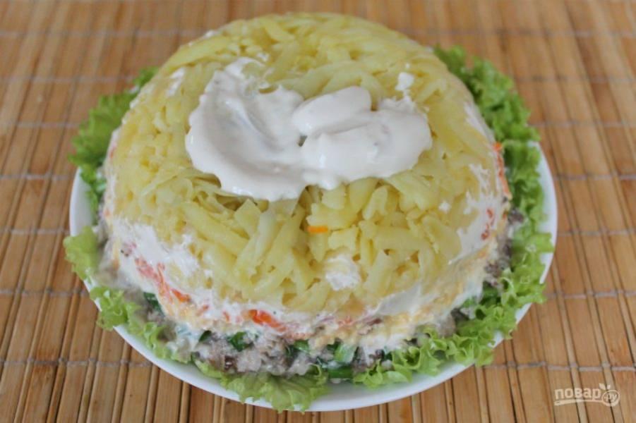 Пиалу с салатом накрываем плоской тарелкой, переворачиваем и салат остается на плоской тарелке. Пищевую пленку удаляем. Слой картофеля смазываем майонезом.