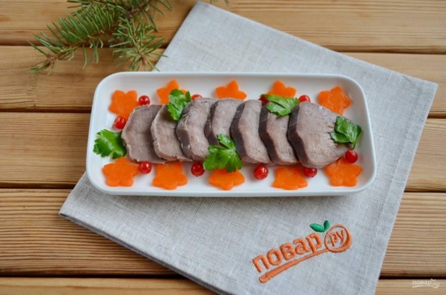 Возьмите тарелочки с высокими бортиками. Разложите на них язык и украшение. У меня это цветочки из вареной моркови, ягоды калины, петрушка.