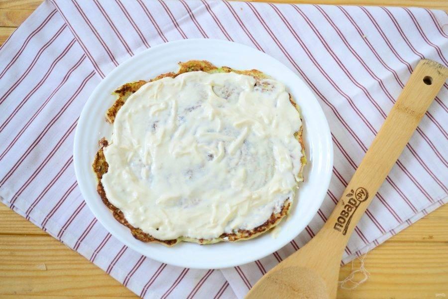 Начинаем собирать торт. На тарелку, подходящую по размеру, положите первый блин, смажьте его сметанным соусом.