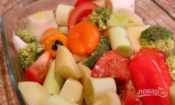 Все овощи промойте, почистите те, которые необходимо, и крупно нарежьте. Овощи уложите в жаропрочную форму. Посолите их, поперчите и влейте немного масла. Запекайте гарнир вместе со свининой в течение 30 минут.