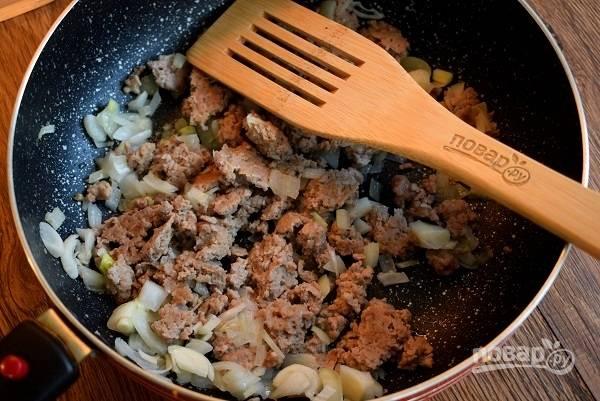 Лук и чеснок измельчите. На разогретом растительном масле обжарьте фарш и овощи в течение 5 минут.