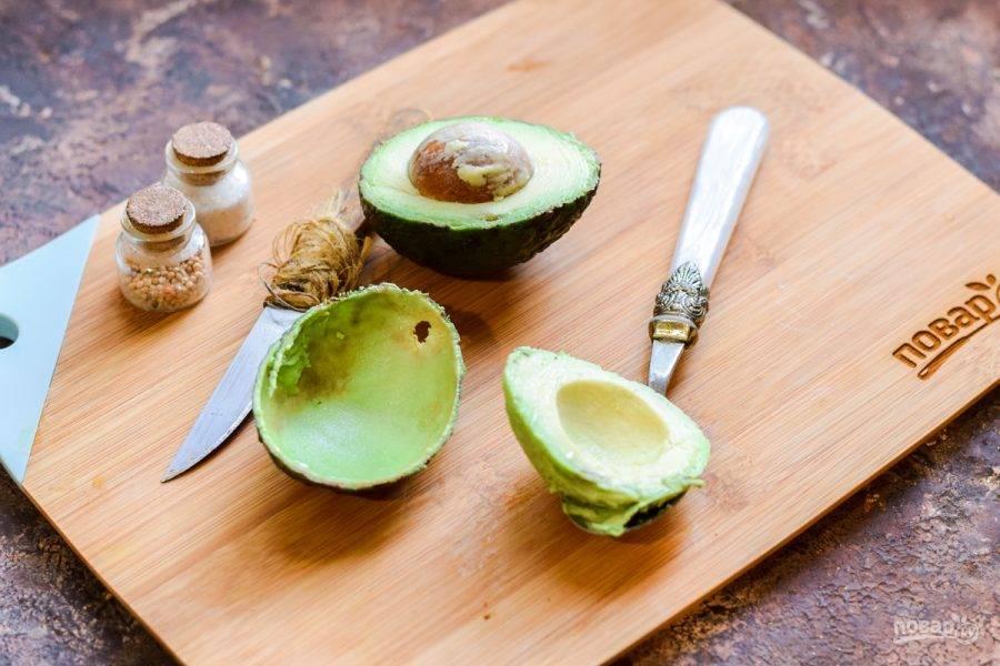 Авокадо разрежьте пополам, аккуратно извлеките мякоть при помощи ложки.