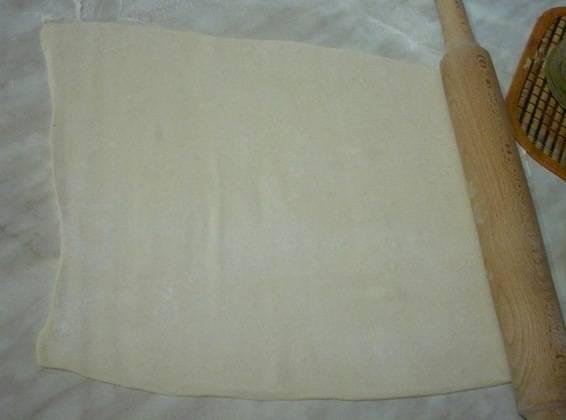 Когда тесто разморозится, выкладываем его на посыпанный мукой стол и раскатываем в более тонкий пласт.