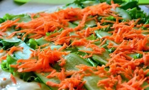 Поверх огурца выкладываем морковку по-корейски.