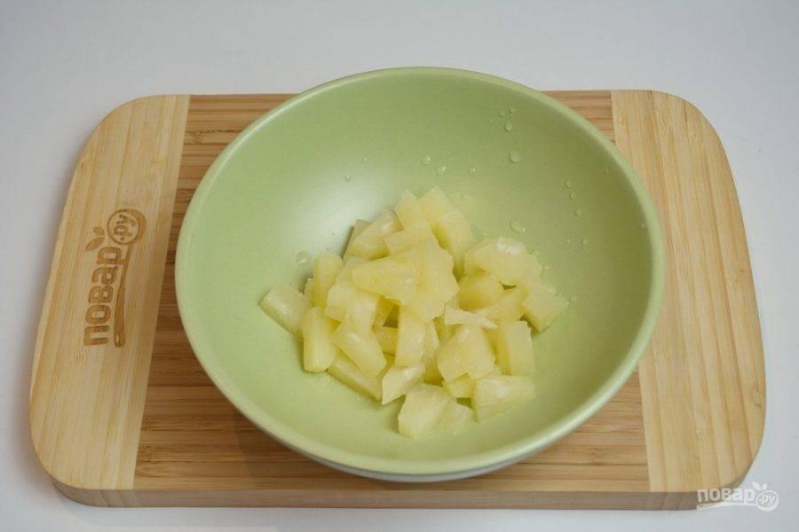 Для приготовления блюда возьмите ананасы. Нарежьте их на кольца, а после на небольшие кусочки. Можно взять консервированный ананас и тоже нарезать его на более мелкие кусочки.
