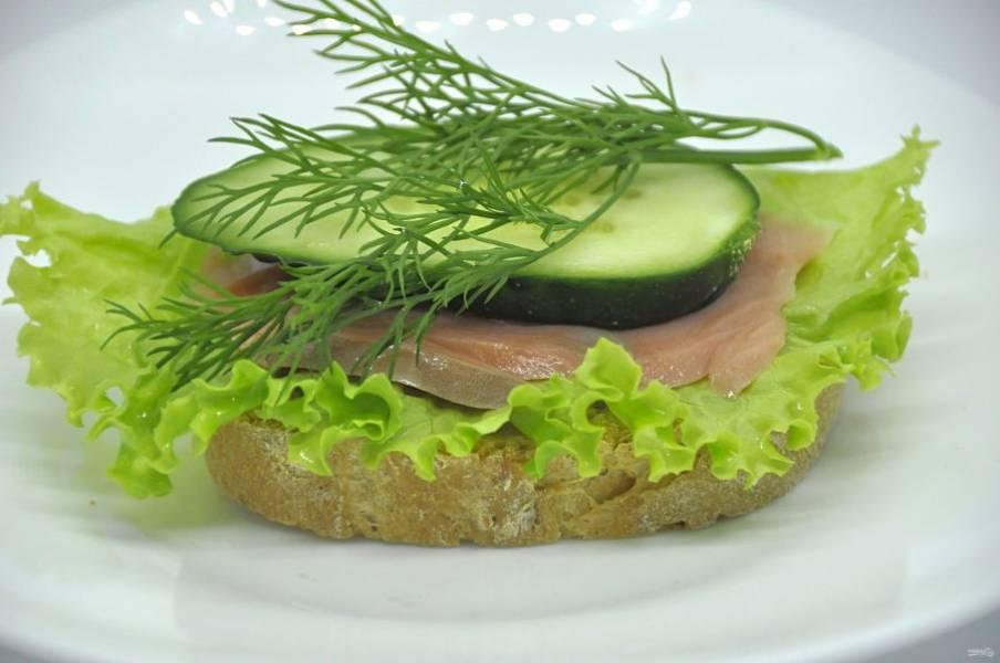 Третий вариант бутербродов: хлеб, салатный лист, ломтик красной рыбы, ломтик огурца, веточка укропа.