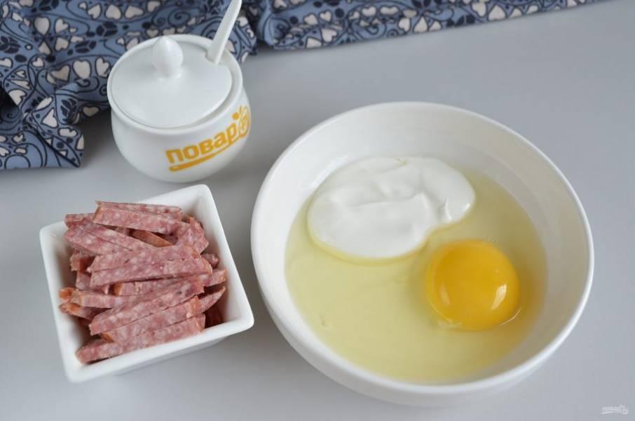 Пока тесто подходит, подготовьте начинку для булочек: колбасу порежьте соломкой, яйцо соедините со сметаной и щепоткой соли.