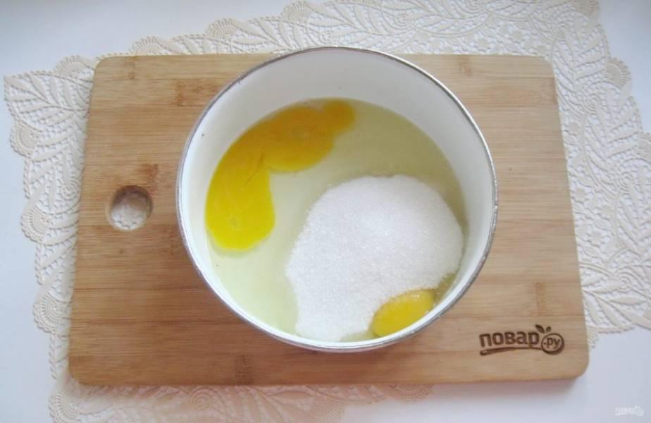 В миску вбейте яйца и всыпьте 150 грамм сахара.