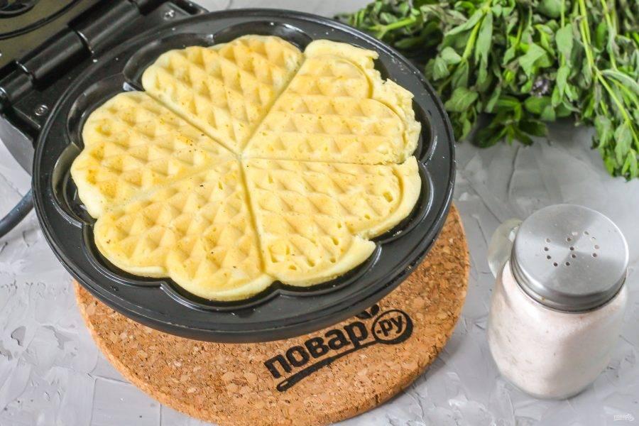 Тщательно прогрейте вафельницу, смазав ее панели растительным маслом. Выложите 1,5 ст.л. теста на панель и закройте вафельницу, испеките десерт примерно 2-3 минуты до румяности.