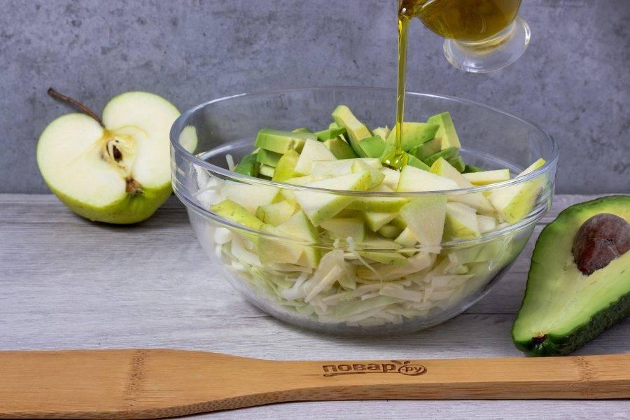 Сбрызните яблоко и авокадо лимонным соком. Заправьте салат маслом.
